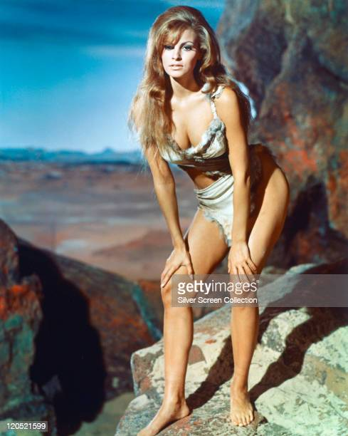 Full-length shot of Raquel Welch, US actress, wearing an animal hide bikini, crouching with her hands on her knees, in a publicity portrait issued...