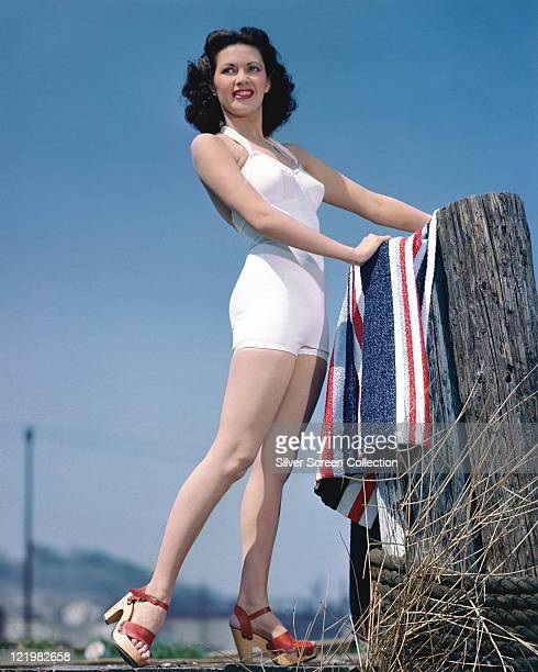 Fulllength shot of Yvonne De Carlo Canadian actress wearing a white swimsuit while placing a red white and blue striped towel on a wooden post circa...