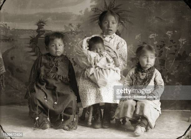 Fulllength studio portrait in front of a painted backdrop of a HoChunk boy posing sitting on the left wearing a fringed leather dress Black River...