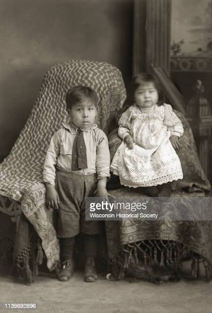 Fulllength studio portrait in front of a painted backdrop of a HoChunk boy standing and girl Black River Falls Wisconsin 1916 The boy is wearing...