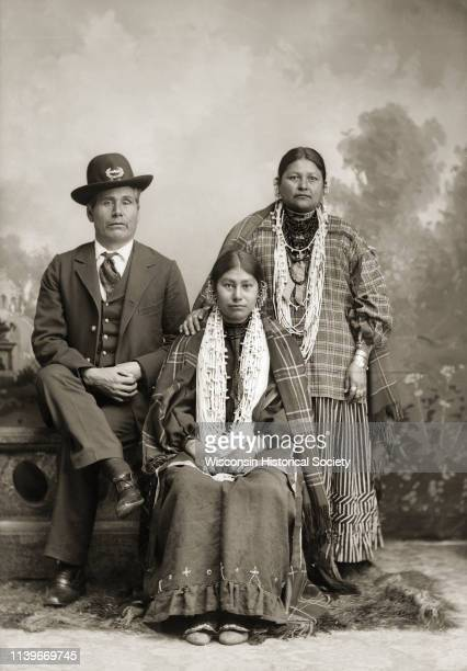 Fulllength studio portrait in front of a painted backdrop of a European American man and two HoChunk women Black River Falls Wisconsin 1900 The man...