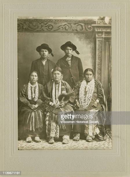 Fulllength studio portrait in front of a painted backdrop of three HoChunk women posing sitting in a row wearing several necklaces earrings file...