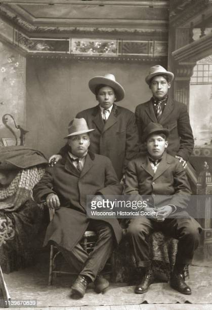 Fulllength studio portrait in front of a painted backdrop of two HoChunk men posing sitting in front of two HoChunk men posing standing Black River...