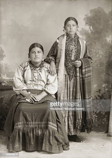 Fulllength studio portrait in front of a painted backdrop of two young HoChunk women Ida Lizzie Decorra Blowsnake sitting with halfsister Johanna...