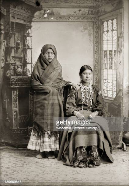 Fulllength studio portrait in front of a painted backdrop of two HoChunk women Black River Falls Wisconsin 1885 The woman on the left possibly Miss...
