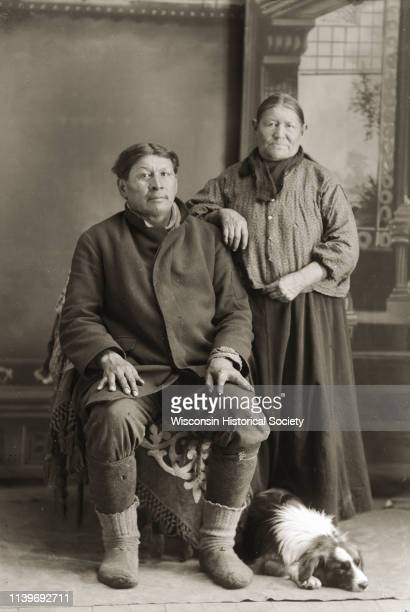 Fulllength studio portrait of a HoChunk couple John Buffalohead and wife Mary Snowball Decorra Buffalohead with their dog lying at their feet Black...