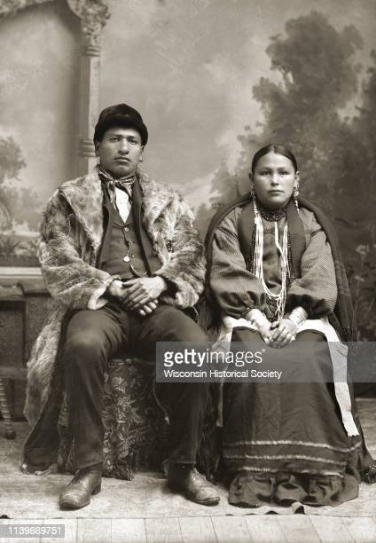 Fulllength studio portrait of a HoChunk man and his wife posing sitting in front of a painted backdrop Black River Falls Wisconsin 1895 He is wearing...