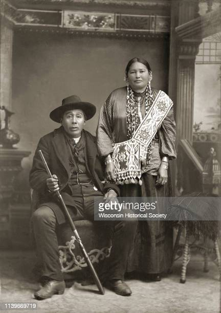Fulllength studio portrait of a HoChunk man George Greengrass and his wife in front of a painted backdrop Black River Falls Wisconsin 1900 George...