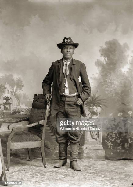 Fulllength studio portrait of a HoChunk man posing standing next to a chair identified as Homer Snake who is wearing a hat with a GAR emblem...