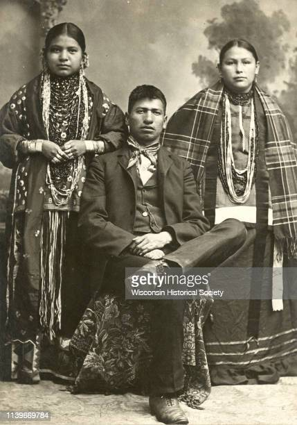Fulllength studio portrait of a HoChunk man sitting and wearing modern dress flanked by two HoChunk women standing and wearing several necklaces and...