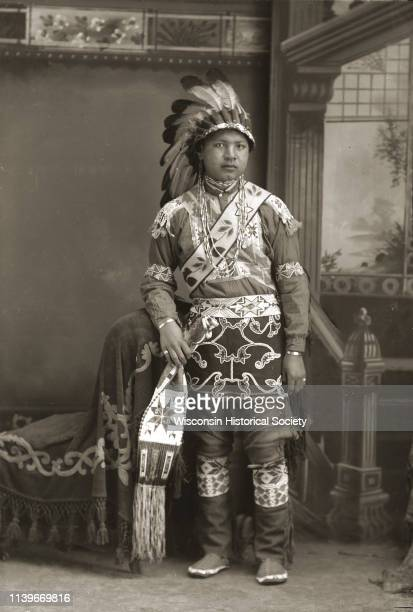 Fulllength studio portrait of a young HoChunk man posing in front of a painted backdrop Black River Falls Wisconsin 1912 Benjamin Raymond...