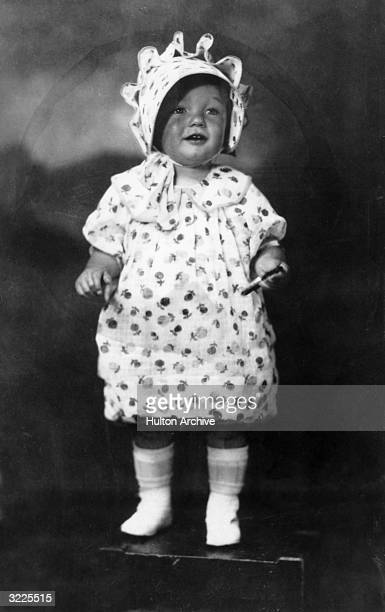 Fulllength studio portrait of American actor Marilyn Monroe at the age of two standing on a box in a floral print dress and matching bonnet