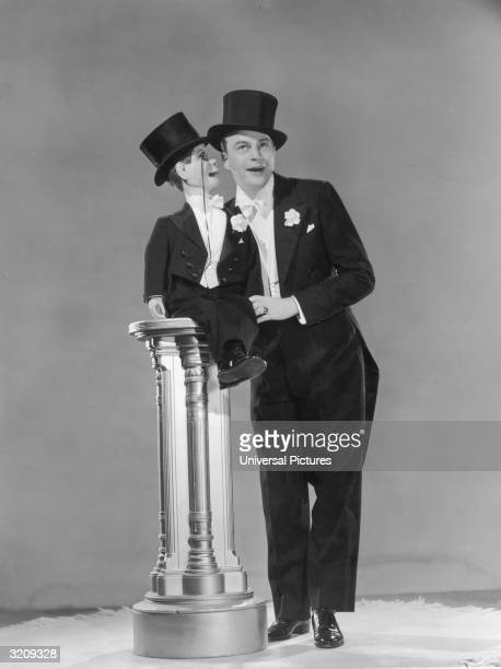 Fulllength studio portrait of American ventriloquist Edgar Bergen listening to his dummy Charlie McCarthy who sits on a pedestal Both white tie and...