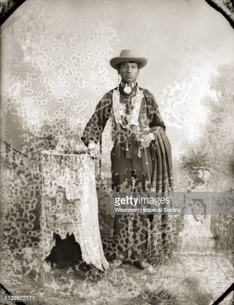 Fulllength studio portrait of Black River Falls Wisconsin 1886 He is leaning on a stump used as a prop in Van Schaick's studio and is adorned with...