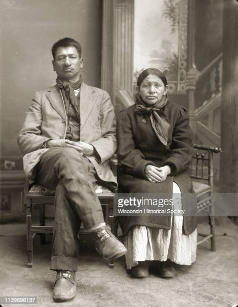 Fulllength studio portrait of Thomas Thunder and his wife Addie Littlesoldier Lewis Thunder Black River Falls Wisconsin 1915 He is wearing a scarf...