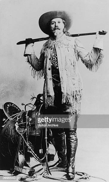 Fulllength studio portrait of William 'Buffalo Bill' Cody standing in front of his saddle holding a rifle behind his back