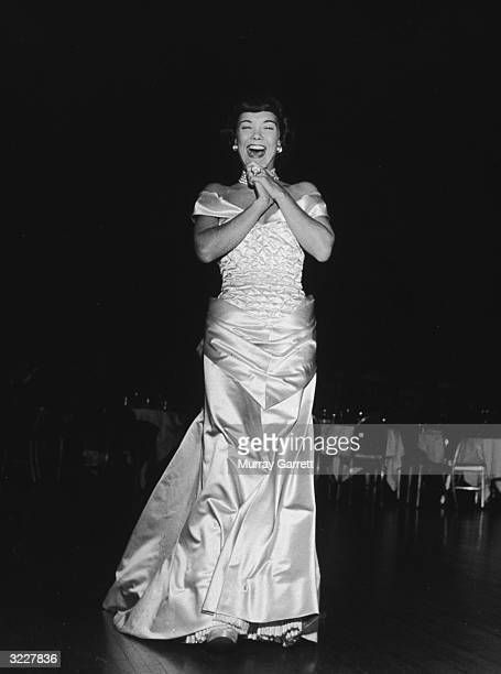 Fulllength view of American actor Jane Wyman clasping her hands and smiling at the opening party for director Jean Negulesco's film 'Johnny Belinda'...