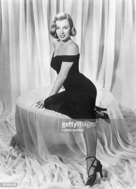Fulllength view of American actor Marilyn Monroe reclining in a black cocktail dress in a promotional portrait for director John Huston's film 'The...