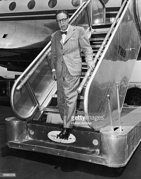Fulllength view of American author and screenwriter Dalton Trumbo walking down a TWA ramp after exiting an airplane La Guardia airport New York...