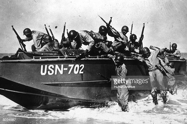 Fulllength view of an AfricanAmerican Seabee battalion preparing to disembark from an amphibious landing craft on a beach during a training exercise...