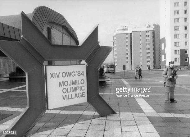 Fulllength view of an armed military officer standing guard at the entrance to the Mojimilo Olympic Village during the Winter Olympic Games in...