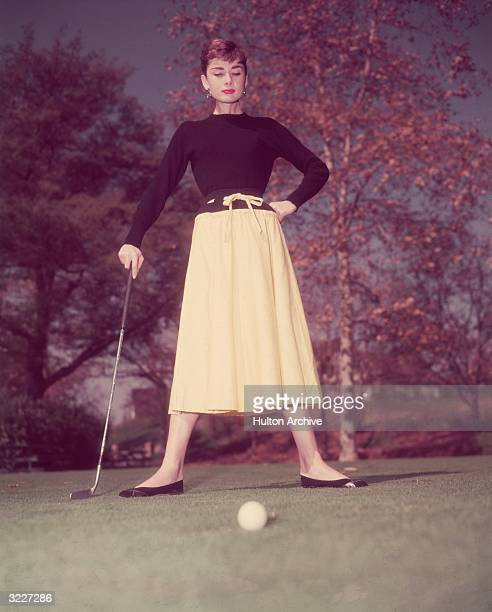 Fulllength view of Belgianborn actor Audrey Hepburn standing on a golf course holding her putter with a golf ball on the green in the foreground She...