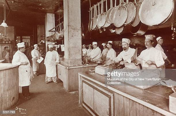 Fulllength view of cooks wearing aprons and chef hats preparing food behind two long counters in the kitchen of Delmonico's restaurant at the...