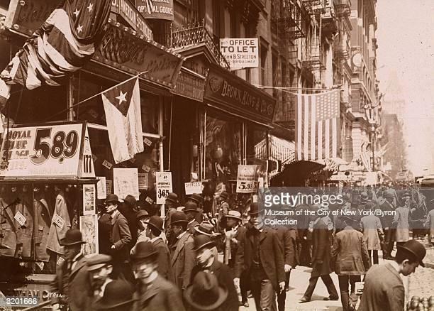 Fulllength view of men most wearing derby hats congregating in front of shops on Broadway facing north on Cortlandt Street New York City