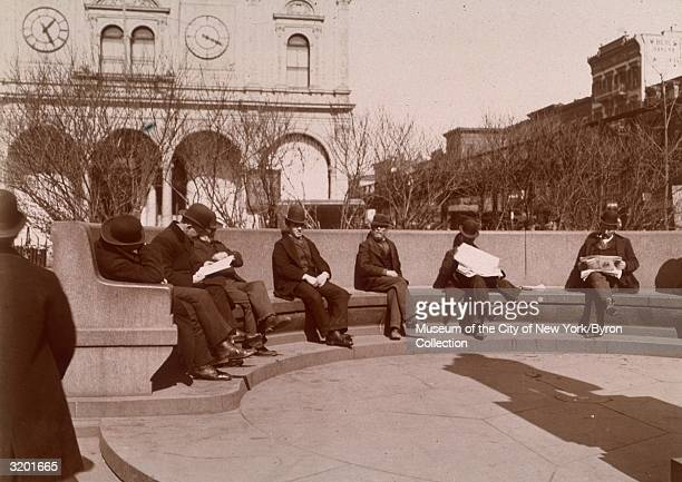 Fulllength view of men some reading newspapers seated on a circular granite bench at Herald Square near 34th Street New York City