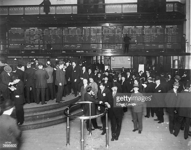 Fulllength view of traders on the floor of a stock exchange while a man posts updated figures for commodities such as wheat cotton oil corn oats and...
