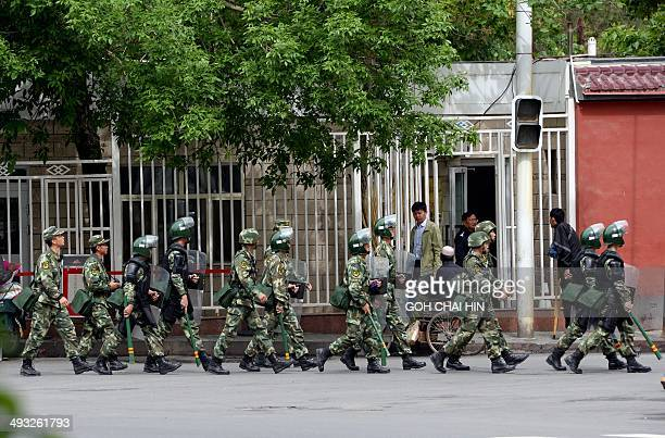 Fully armed Chinese paramilitary police patrol a street in Urumqi the capital of farwest China's Muslim Uighur homeland of Xinjiang on May 23 2014...