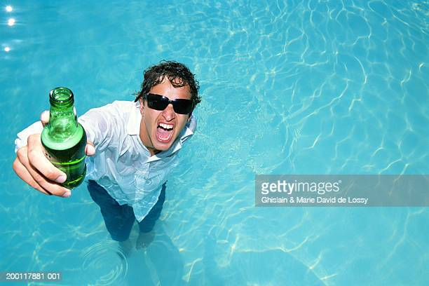 Fully clothed young man in pool with beer bottle, portrait