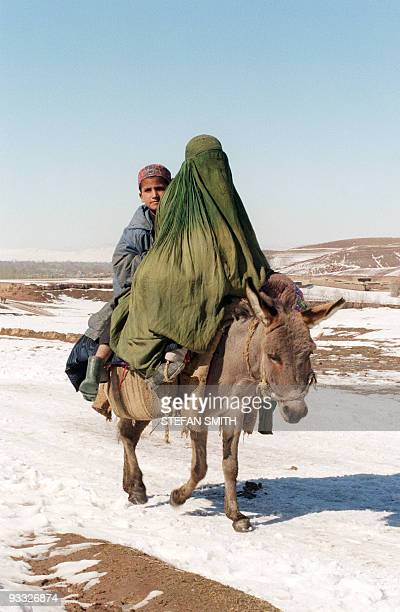 A fully covered Afghan woman and a young boy from the northeastern town of Rostaq travel by the most effective means available in the snow and mud...