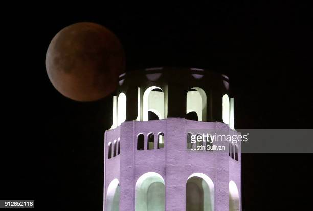 A fully eclipsed super blue blood moon sets behind Coit Tower on January 31 2018 in San Francisco California The 'super blue blood moon' is a rare...