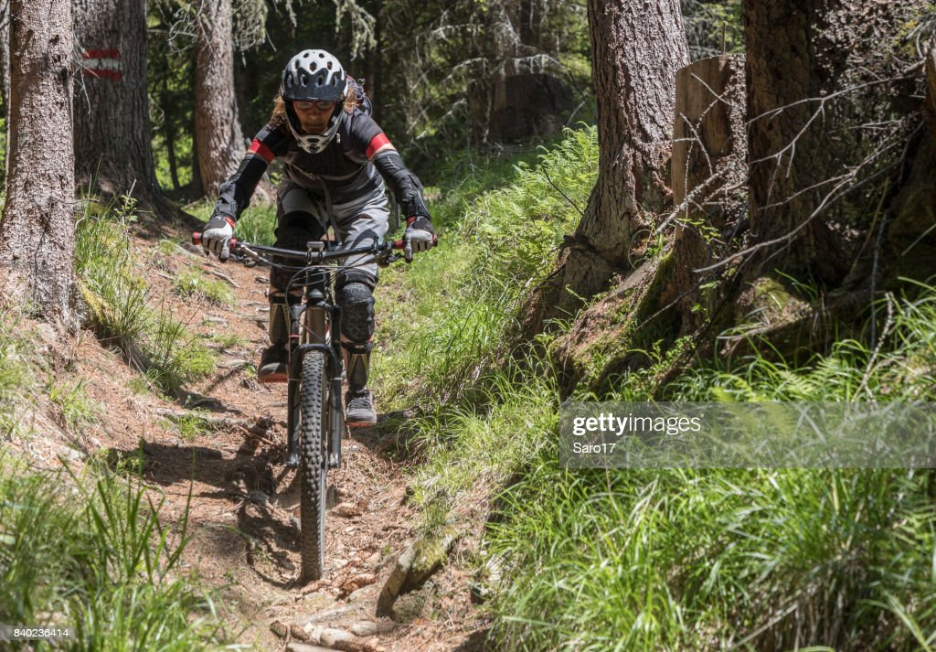 Fully equipped female montainbiker in the Carinthian forests, Austria. : Stock Photo