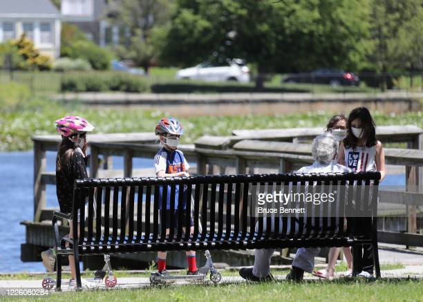 Fully masked children play in Lofts Pond Park on May 20 2020 in Baldwin New York All 50 states are at least partially reopened as reported cases of...