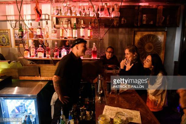 Fully vaccinated customers Julie Brown and Kelsi Teramae talk with a bartender inside Risky Business, that was once The Other Door but closed during...