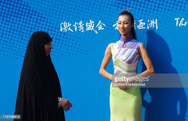 Fully veiled Iranian woman walks past a Chinese hostess during the medals ceremony of the women's 50m Rifle 3 Positions individual shooting...