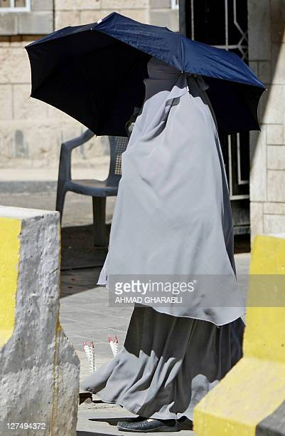 A fully veiled Muslim woman walks between concrete blocks outside a heavily guarded government office in Sanaa on January 7 2010 US military...