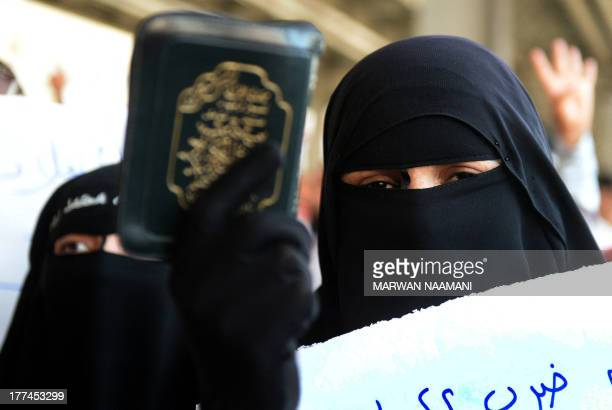 A fully veiled supporter of Egypt's toppled president Mohamed Morsi holds a copy of the Koran Islam's holy book during a demonstration against the...