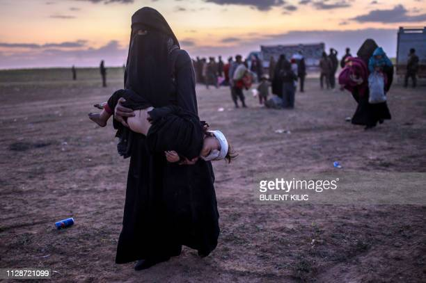 Fully veiled woman carries her injured child as she walks to members of the Kurdish-led Syrian Democratic Forces just after leaving the Islamic State...