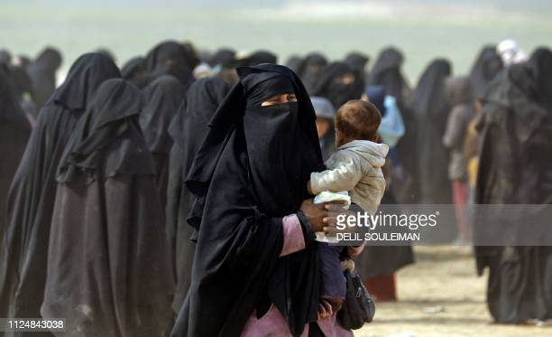 TOPSHOT A fully veiled woman holds her baby as civilians fleeing the Islamic State's group embattled holdout of Baghouz walk in a field on February...