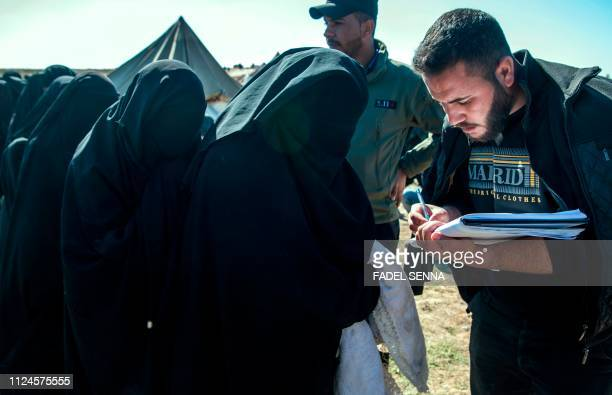 TOPSHOT Fully veiled women fleeing from the Baghouz area in the eastern Syrian province of Deir Ezzor give out their names on February 12 2019 during...