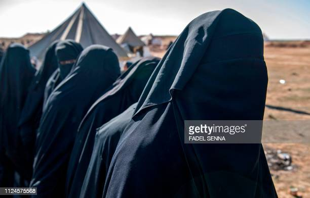 Fully veiled women fleeing from the Baghouz area in the eastern Syrian province of Deir Ezzor queue up on a field on February 12 2019 during an...