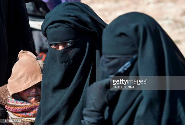 Fully veiled women fleeing from the Baghouz area in the eastern Syrian province of Deir Ezzor queue up in a field on February 12 2019 during an...