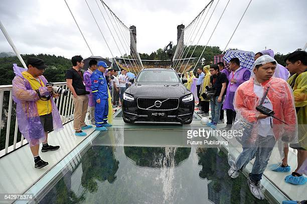 Fully-loaded Volvo sedan runs on the glass-floored suspension bridge after men cracked the glass with sledgehammers during a test on June 25, 2016 in...