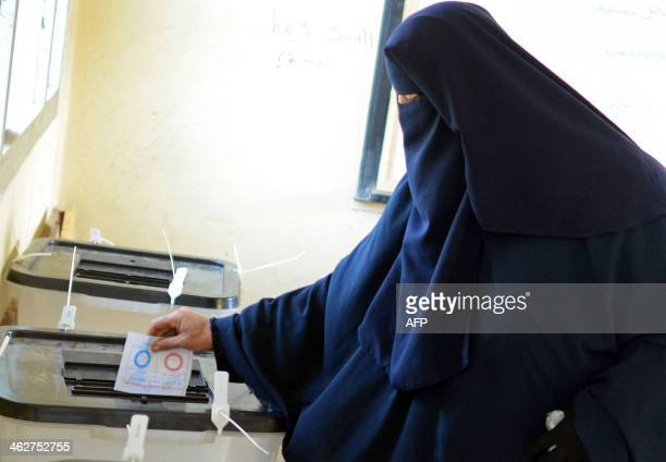 A fullyveiled Egyptian woman casts her ballot at a polling station in Cairo during the second day of voting on a new constitution on January 15 2014...