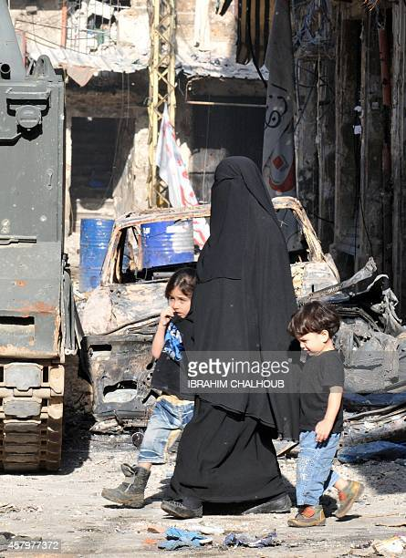 A fullyveiled Lebanese woman walks with her children along a damaged street in Tripoli's Bab alTabbaneh Sunni neighbourhood on October 28 2014 after...