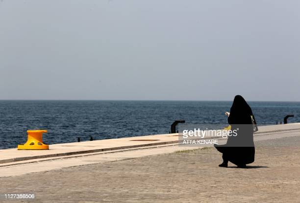 A fullyveiled woman walks by the dock at the Shahid Beheshti Port in the southeastern Iranian coastal city of Chabahar on the Gulf of Oman on...
