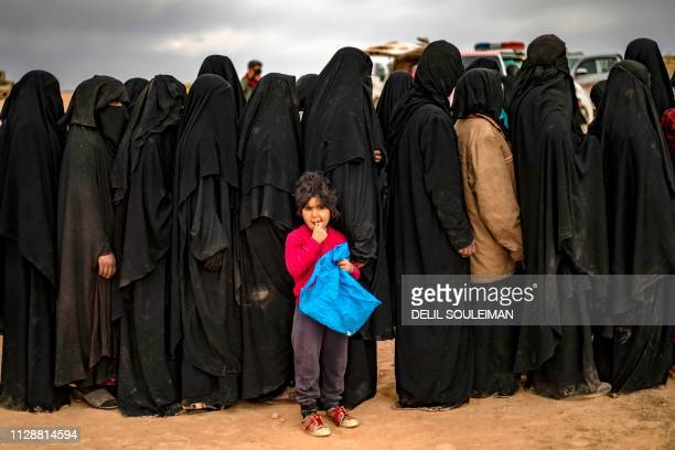 Fully-veiled women and children queue at a screening point as hundreds of civilians, who streamed out of the Islamic State group's last Syrian...